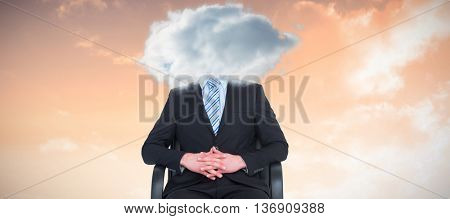 Stern businessman sitting on an office chair against sunset with clouds