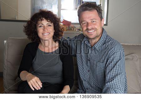 Cheerful Couple On Sofa Smiling At Camera
