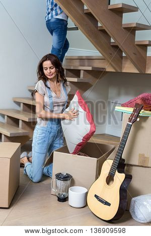 Woman unpacking cushion from cardboard box at home