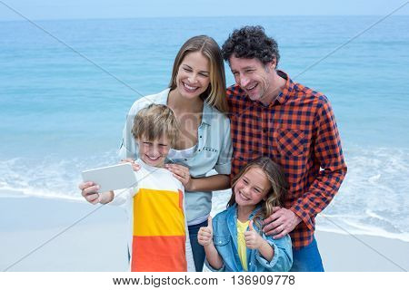 Happy family taking selfie while standing at sea shore