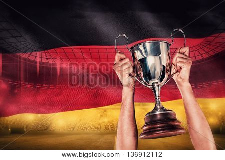 Portrait of smiling rugby player holding trophy against digitally generated german national flag