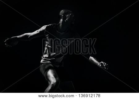 Athlete man throwing a discus against black background