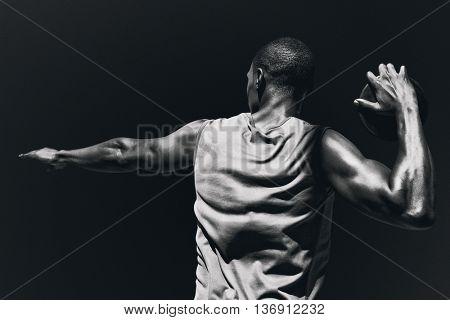 Rear view of sportsman practising discus throw against black background