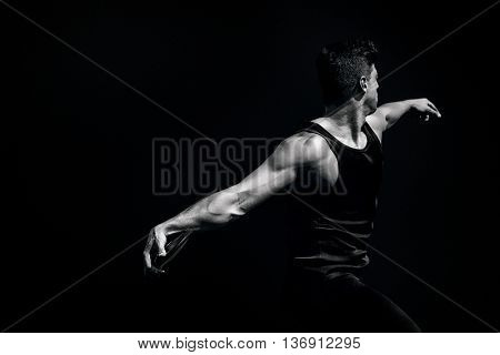 Side view of man throwing discus against black background