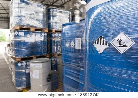 Waste barrels with hazard warning symbols in the warehouse