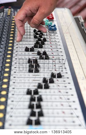 Part of a professional sound mixing console hand controls the slider music device for audio signal