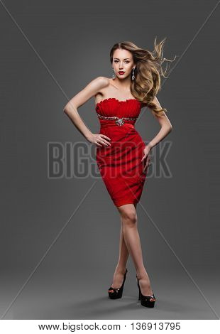 Fashion Model Hair Waving on Wind Young Woman Posing In Gray Studio Red Dress