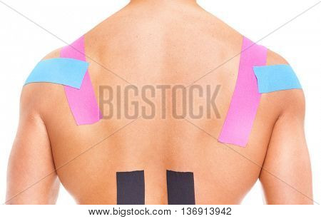 Muscular man with kinesiotaping on the shoulders and lower back, isolated on white background