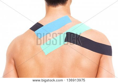 Young muscular man with kinesiotaping on the shoulders and back, isolated on white background