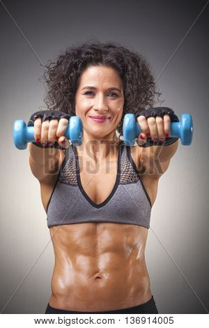 Fit woman lifting weights on grey bakground