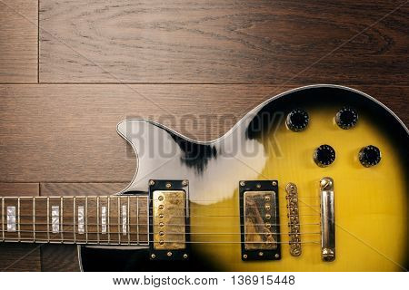 Black and yellow electric guitar on wooden brown surface. Closeup