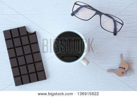 Topview of wooden desktop with cup of coffee bitten chocolate bar glasses and keys. 3D Rendering