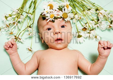 wide-awake newborn baby lying on a green background with a bouquet of daisies and a wreath of flowers on her head. Naked baby with a healthy beautiful skin. Portrait of a little girl with gray eyes.