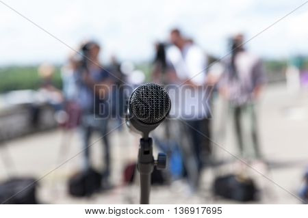 Microphone in focus against blurred camera operators. News conference.