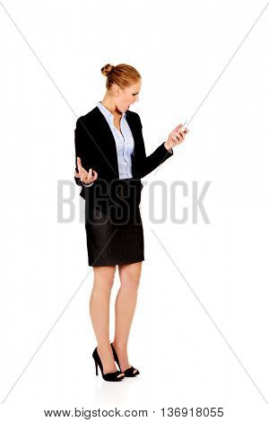 Angry business woman yelling to the mobile phone