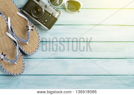 Beach accessories. Flip flops, camera and sunglasses on wooden background. Top view with copy space. With sun beam