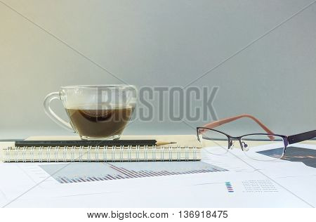 Closeup black coffee in transparent cup of coffee on note book and pencil with work paper on blurred wooden desk and glass wall textured background work concept by coffee work paper and eyeglasses