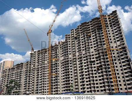 New high-rise modern apartment buildings construction in process ob bright sunny day front view horizontal