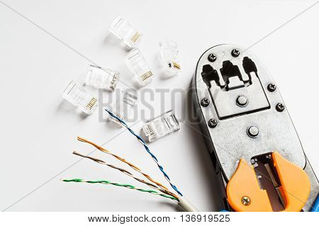 Crimper connectors and ethernet cable on white background