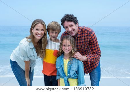 Portrait of happy parents standing with children on shore at beach