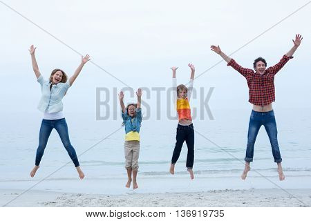 Full length of family jumping with arms raised at sea shore