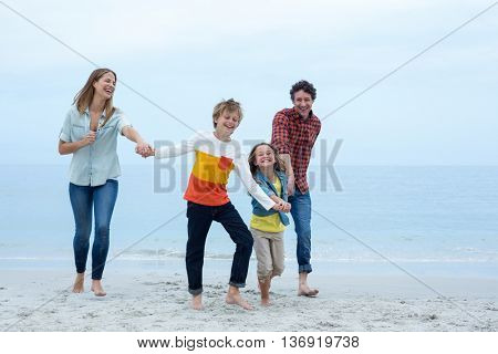 Full length of cheerful family holding hands while running at sea shore
