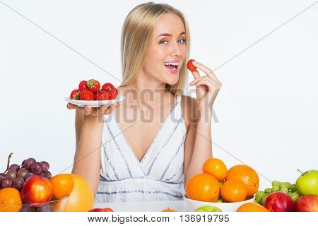 Smiling pretty young woman eating strawberries