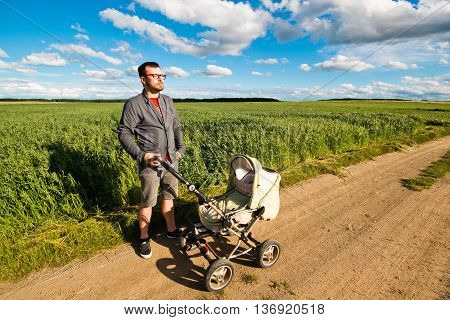 young father walking with a baby stroller on nature. Parenting and fatherhood on maternity leave.