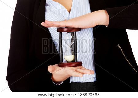Young business woman holding hourglass-time concept