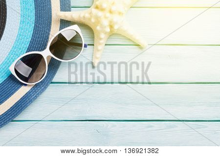 Beach accessories. Hat, sunglasses and starfish on wooden background. Top view with copy space. With sun beam