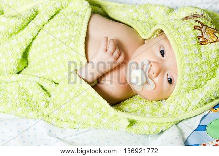 Newborn baby lying in a hooded towel after taking a bath. Bathing children. Children's Care.
