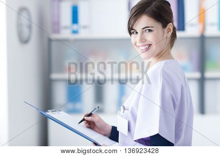 Smiling Doctor Writing Medical Reports