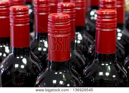 Closed red wine bottles standing in stores stock.
