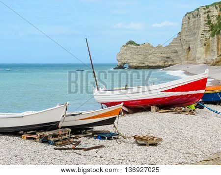 Colorful fishing boats ashore of English Channel and famous cliff La Falaise d'Amont as background. Etretat, Normandy France