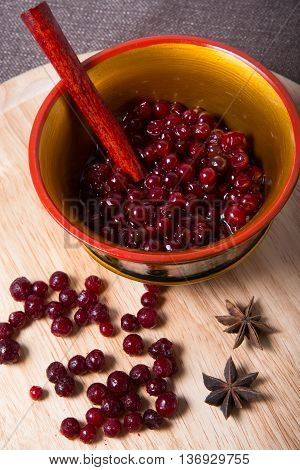 Frozen cranberry on wooden board and russian ethnic bowl