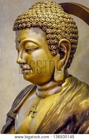 The world famous Gautama Buddha, also known by the name Siddhartha Gautama, Shakyamuni Buddha, or simply the Buddha. This image shows a closeup of a bronze statue - for the public's observance.