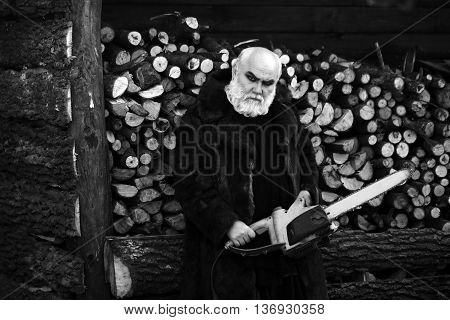 Old bearded man with long silver beard and moustache in fur coat holding big chainsaw sunny day outdoor on wood background black and white