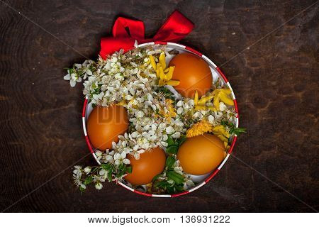 Beautiful wild white and yellow flowers and domestic eggs in decorative round box decorated with red bow
