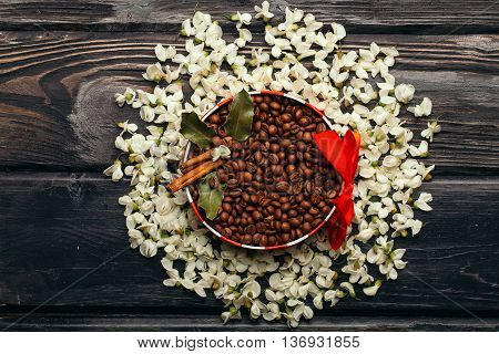 Coffee beans in decorated bowl in white acacia blossoming flower petals round frame on dark wooden background
