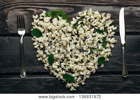 Fork and knife of stainless steel with heart wreath of white acacia blossoming flower petals green leaves on dark timber background