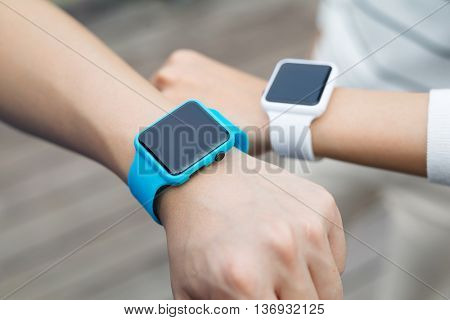 Couple comparing time on smart watch with other
