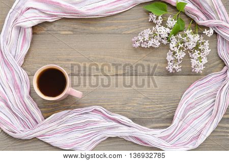 Pink cup with tea lilac and table-napkin on a wooden background. Focus is on the cup of tea. Copy space composition.