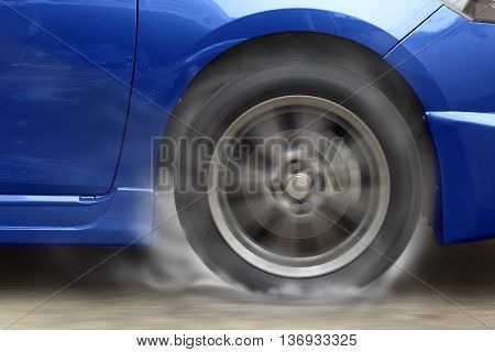 Blue car racing spinning wheel burns rubber on floor.