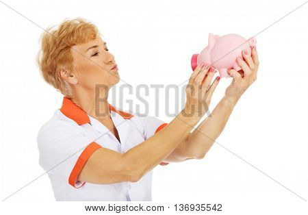 Smile elderly female doctor or nurse holding piggybank