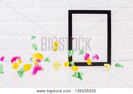 Decorative see-through picture frame and colorful crumpled paper pieces on white brick background. Mock up