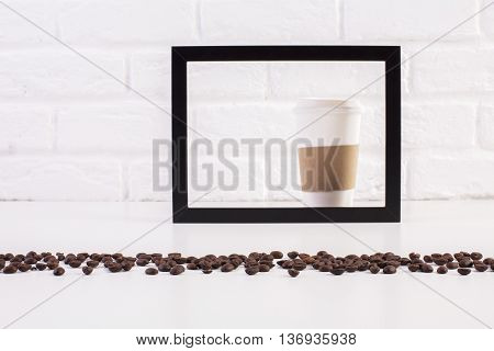 Closeup of white table with coffee beans and take away coffee cup inside black picture frame on white brick background