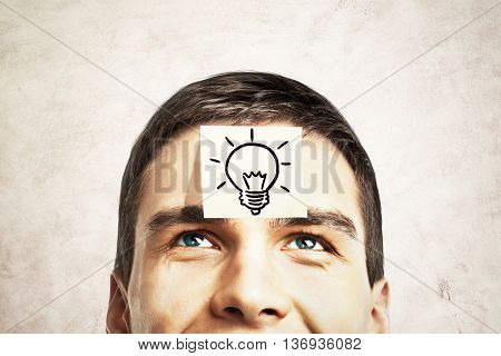 Idea concept with lightbulb sketch drawn on sticker glued to happy guy's forehead on concrete background