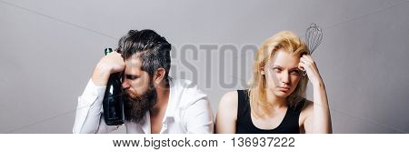young family couple of blonde pretty girl with beater and bearded man with long beard holding wine bottle on grey background. household everyday life and routine