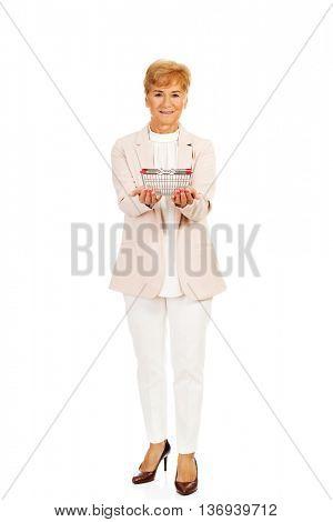 Smile elderly woman holding small shopping basket