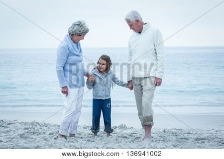 Happy grandparents with granddaughter at beach against sky